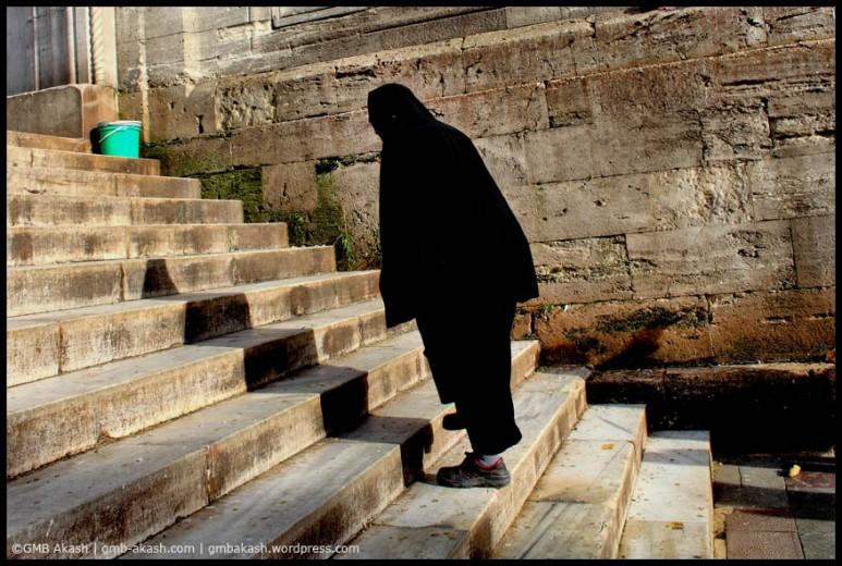 A woman is stepping towards stairs of mosque