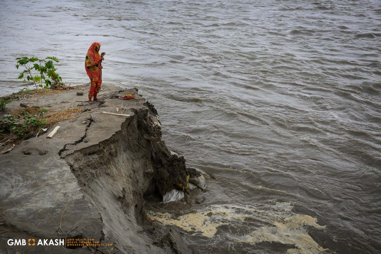 A woman stands beside the River Jamuna where erosion is eating into its banks.