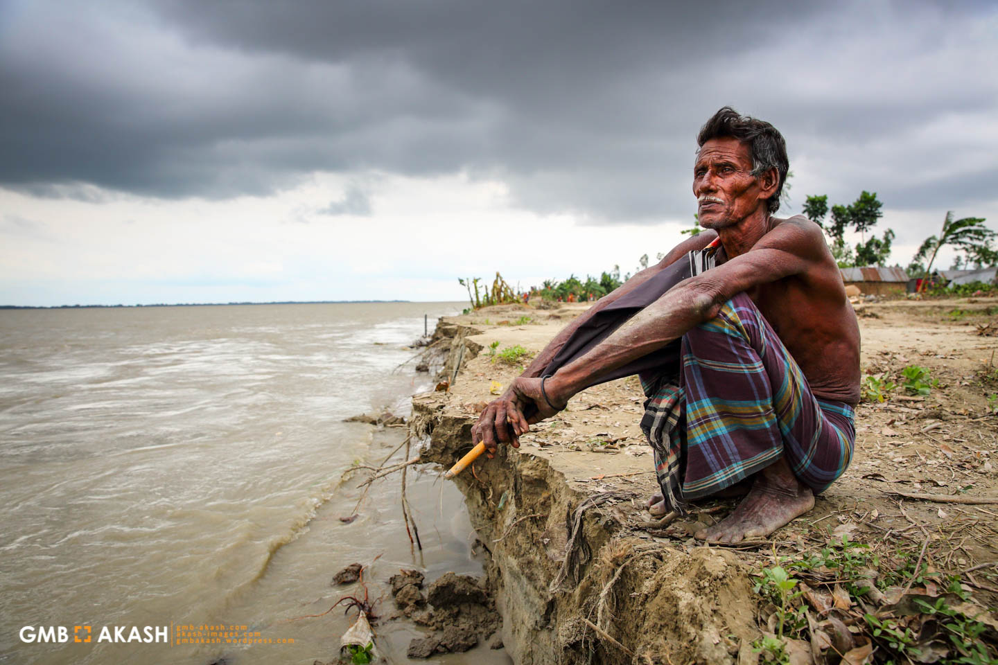 Shaha Ali (60), a resident of Sariyakandi sits on the banks of the Jamuma River where his house once stood before the eroding river banks caused it to collapse (1)